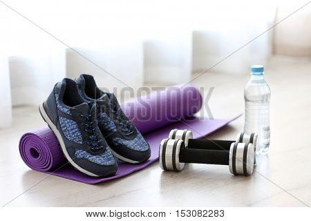 Comfortable sneakers with sport tools on floor