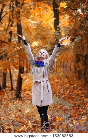 laughing girl with long blonde hair throws leaves in autumn park. Happy woman playing with autumn leaves in forest. Happiness carefree leisure concept. Blond woman relaxing in autumn park throwing leaves up in the air. Beautiful girl in orange forest foli