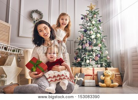 Merry Christmas and Happy Holidays! Mom and her cute daughters girls with gifts. Parent and children having fun and playing together near Christmas tree indoors. Loving family with presents in room.
