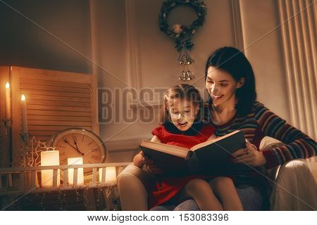 Merry Christmas! Pretty young mother reading a book to her daughter.