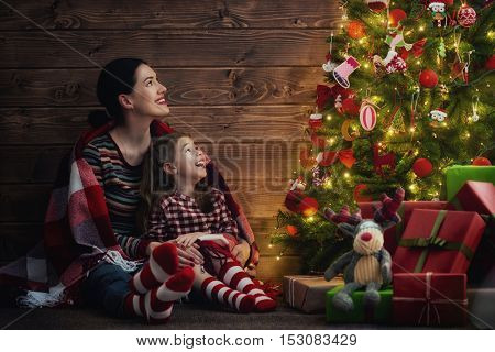 Merry Christmas and Happy Holidays! Loving family mother and child girl near Christmas tree indoors.