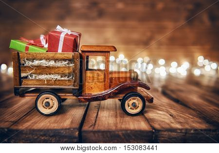 poster of Merry Christmas and Happy Holidays! Gifts boxes presents on toy car and Christmas garland lights on