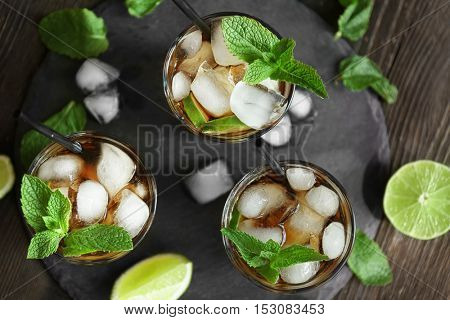 Glasses of cocktail with ice and mint on wooden table, top view