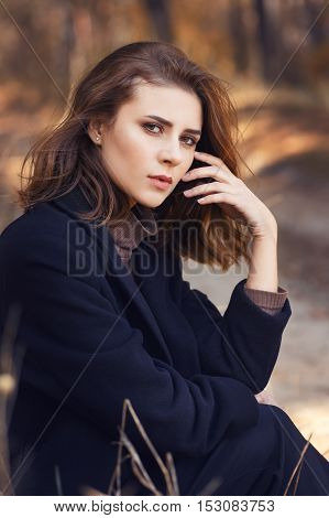 Fashion style portrait of young beautiful elegant woman in black coat. Beautiful sad girl in autumn clothes outdoor on autumn day. Autumn fashion woman wearing trendy coat. Close-up portrait of beautiful brunette woman outdoors