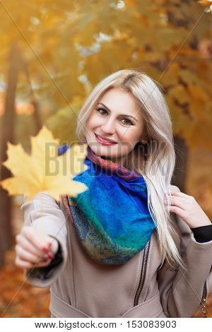 Girl holding autumn orange maple leaf. Portrait of beautiful young blond woman with maple leaf in her hand spending time in autumn park with sunshine. Smiling girl holding yellow maple leaf on the background colorful autumn forest. Autumn