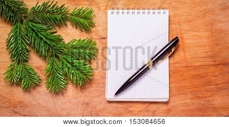 Pen And Notepad On Old Rustic Table Decorated With A Fir Branch.