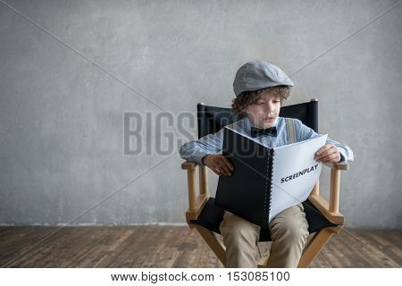 Little child with a screenplay in studio