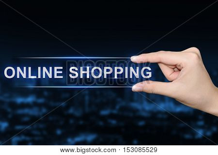 hand pushing online shopping button on blurred blue background