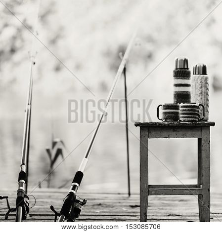 Black-and-white photo. Fishing on the river. A fishing rod and a thermos with cups in knitted covers.