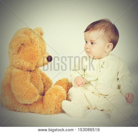 Little Boy Baby Sitting Next To A Teddy Bear