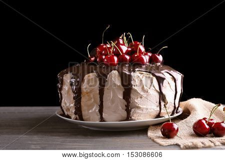 Cake with caramel and cherries on dark background