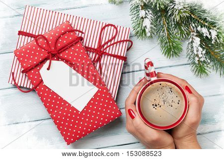 Female hands holding coffee cup, christmas gift boxes and snow fir tree above wooden table. Top view with copy space