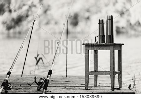 Black-and-white photo. Fishing on the river. A fishing rod and a thermos with cups.