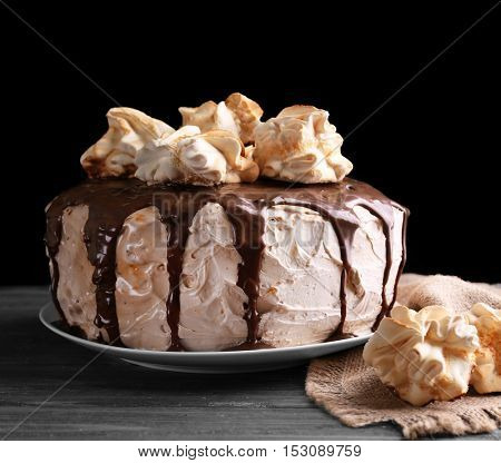 Cake with caramel and meringues on dark background