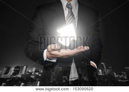 Businessman with turn up bright arrow on hand, with defocus night city background