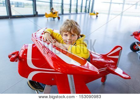 Adorable little preschool kid boy driving big toy old vintage pedal plane and having fun, indoors. Active leisure with children during school holidays