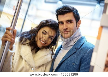 Portrait of attractive young happy couple in entrance.