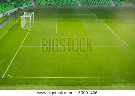 Football field corner with white marks, green grass texture in soccer field and corner flag.