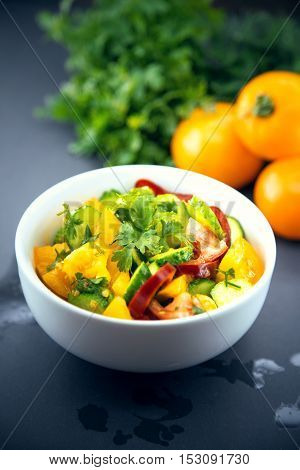Close Up of colorful salad from tomatoes cucumbers peppers and herbs in the white ceramic bowl on gray stone table. Vegetarian food. Organic vegetables.
