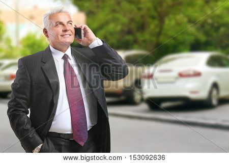 Businessman talking on phone outdoor. Car sale and rent concept.
