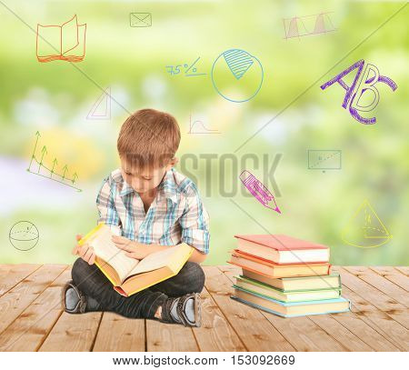 Cute little boy with book sitting on wooden floor against blurred background. Diversity of school icons on background.