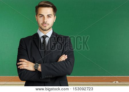 Young teacher on chalkboard background. School and education concept.