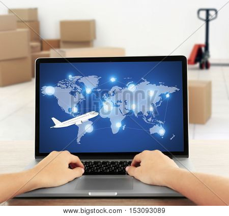 Woman working with laptop against storehouse background. Worldwide transport logistic network on screen. Wholesale and retail concept.