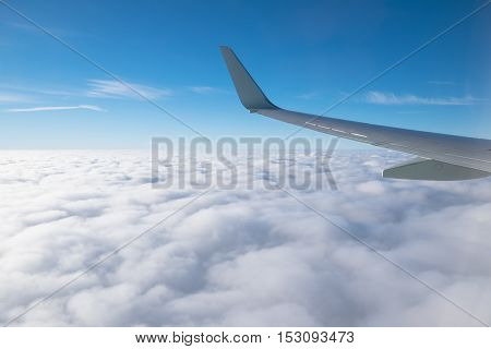 Wing aircraft in altitude during flight. Blue sky and white clouds
