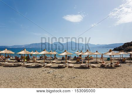 Agios Nikolaos Greece - October 10 2016: Some people are resting on the beach of resort small town