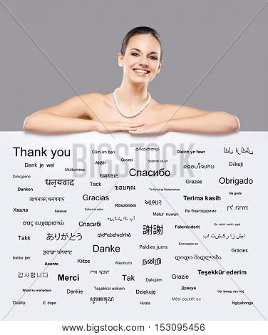 Beautiful smiling girl with a billboard of world's different languages over grey background.