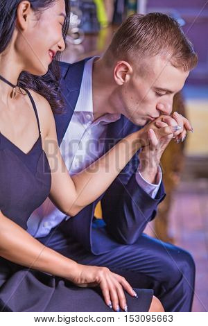 Very elegant and stylish multi racial being together in their house, the man is kissing her hand out of love and affection