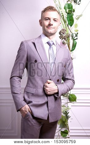 Portrait of attractive man with grey suit against wall