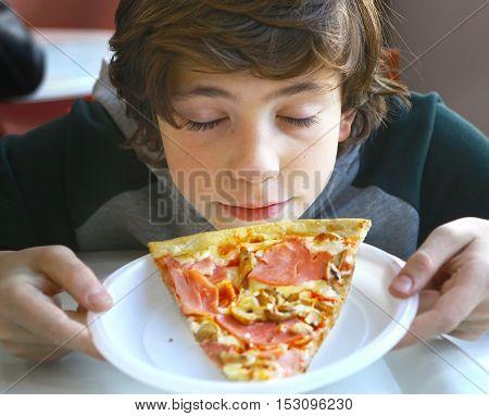 cute little preteen boy smelling pizza close up photo