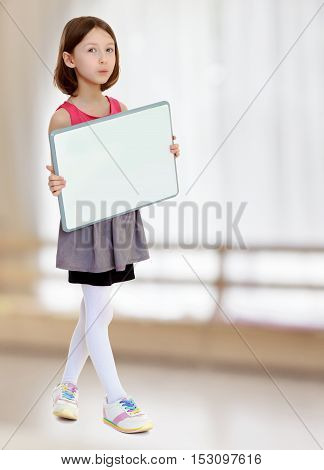 Beautiful, small, slender girl, holding in front of a white poster.In a room with a large semi-circular window.