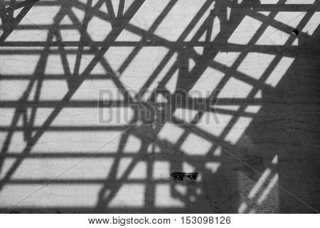 Black and white photoShadows of steel roof frame on building wall.
