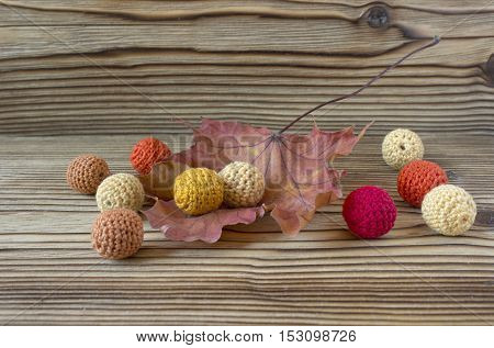 Dry autumn maple leaf on wooden background. Herbarium. Artistic original backdrop place for text. Handmade crochet beads knitting sewing homemade colorful background for sketchbook notebook