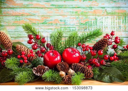 Christmas decoration with fir tree, pine cones, red apples and holly berries