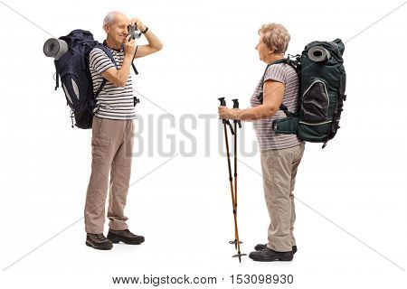 Elderly male hiker taking a picture with a camera of an elderly female hiker isolated on white background