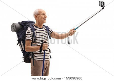 Elderly male hiker taking a selfie with a stick isolated on white background