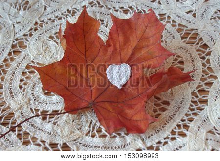 Dry autumn maple leaf and crochet heart on wooden background. Herbarium. Artistic original backdrop place for text copy space