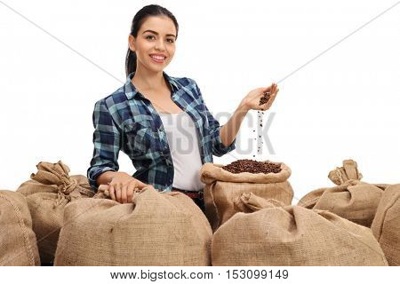 Female farmer posing with a pile of burlap sacks filled with coffee beans isolated on white background