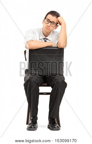 Sad businessman with a leather suitcase waiting for a job interview isolated on white background