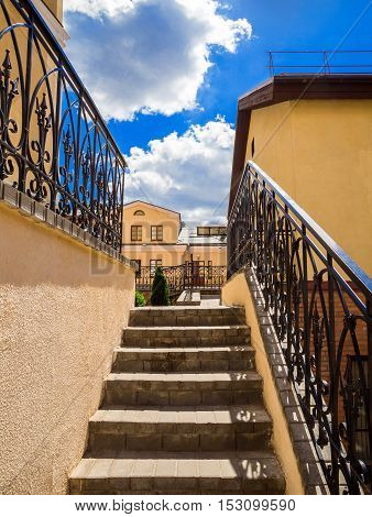 old stairs of concrete outdoors black steel railing with a yellow wall perspective city architecture