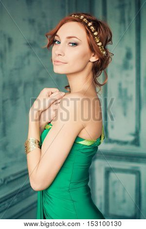 Woman in green evening gown stands in the fashion studio looking on us