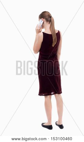 back view of a woman talking on the phone.  backside view of person.  Rear view people collection. Isolated over white background. A girl in a burgundy dress talking on the phone.