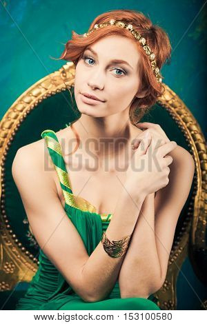 Woman in green evening gown seated looking on us