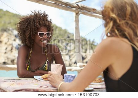 Two female friends sit talking at a table by the sea, Ibiza