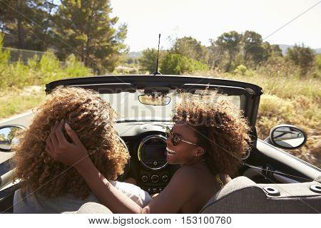 Woman embraces her partner as he drives, rear passenger POV
