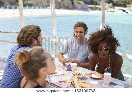 Two female friends talking over drinks at a table by the sea