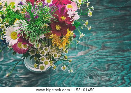 Bouquet of fresh summer flowers on the blue wooden grunge desk. Mock up for greeting cards, holiday postcards, invintation in vintage hipster eco rustic style with copy space